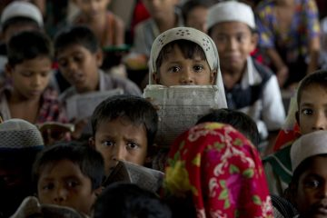 In this Sept. 18, 2013 photo, Muslim children learn the Quran by rote at Rohingya Village Madrassa in The' Chaung Village on the outskirts of Sittwe in Rakhine state, Myanmar. A year after Buddhist mobs forced almost all members of the minority Rohingya Muslim community from Sittwe, creating a state-sanctioned sectarian divide, thousands of children while away their long, empty days in dusty displacement camps. (AP Photo/Gemunu Amarasinghe)