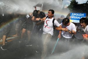 Protesters are hit by a water cannon as they try to march towards the U.S. embassy during a rally against U.S. President Donald Trump's visit, in Manila, Philippines November 12, 2017. REUTERS/Athit Perawongmetha